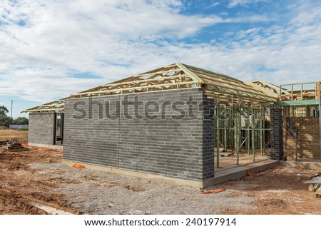 new home currently under construction against blue sky - stock photo