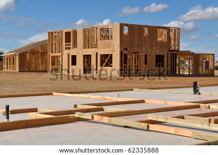 New Home Foundation Foreground with Construction in Background - stock photo