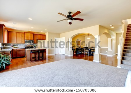 New home kitchen interior and large empty living room. - stock photo
