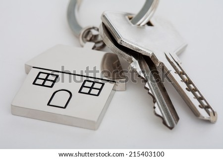 New home mortgage keys and keyring laying on a white desk, close up view. Still life representation of home buying and mortgage commitment, interior. - stock photo