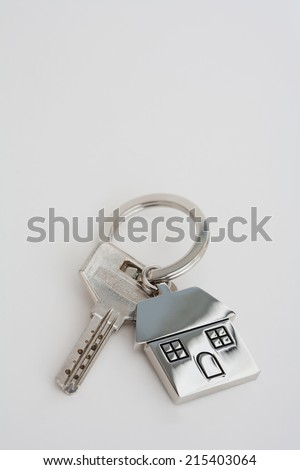 New home owner mortgage keys and keyring laying on a white desk, close up view. Still life representation of home buying and mortgage commitment, interior. - stock photo