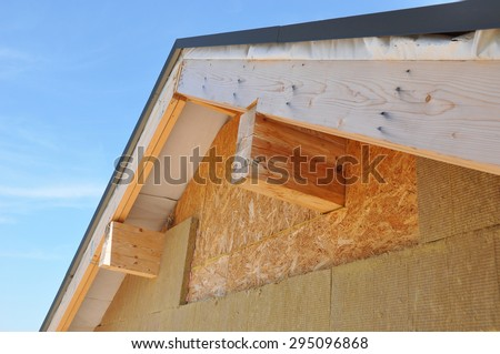 New house wall facade insulation against blue sky. Roof insulation detail. Building insulation, added to buildings for comfort and energy efficiency.  - stock photo