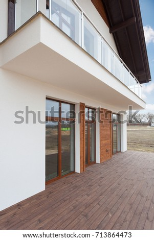 New house with white walls, wooden terrace and 