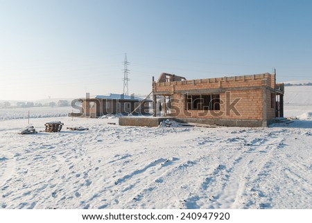 New houses construction in winter. First floor of the new house is built but the construction is stopped due to bad weather conditions - stock photo