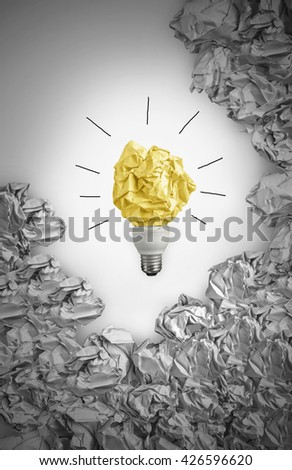 New idea concept with black and white background crumpled office paper and light bulb - stock photo