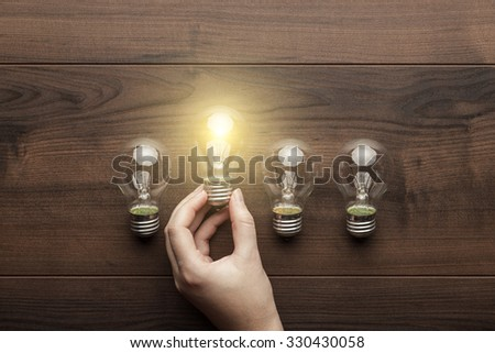 new idea concept with female hand holding light bulb - stock photo