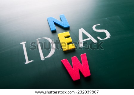 New ideas, words on blackboard with colorful alphabets.