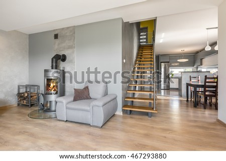 New interior with armchair, fireplace in industrial style, wooden stairs, dining set and open kitchen