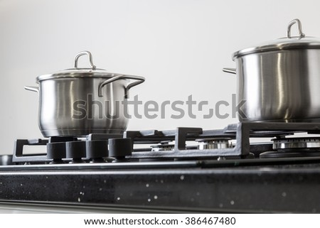 New iron pots on a black gas stove on a kitchen - stock photo