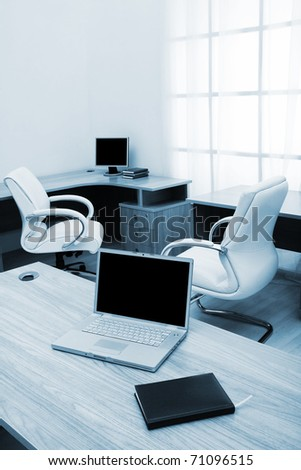 New laptop on a table at modern office - stock photo