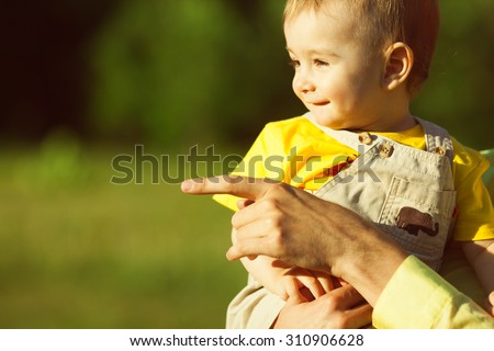 New life born concept. Portrait of cute baby boy sitting in dad's hands and smiling over green forest background. Father is showing something. Sunny summer day. Close up. Copy-space. Outdoor shot