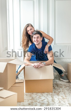 New life in a new home. Couple in love enjoys a new apartment and keep the box in his hands while young and beautiful couple in love sitting on the couch in an empty apartment among boxes - stock photo