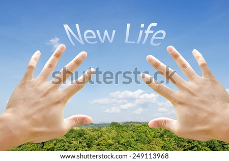 New life word floating on the sky behind hand trying to reach. - stock photo