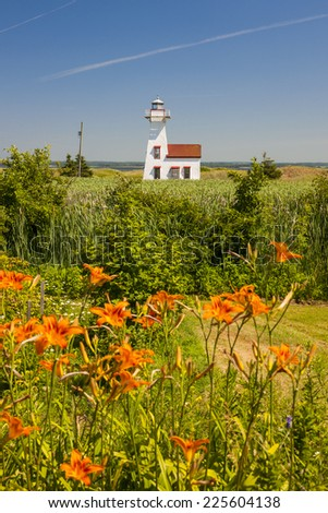 New London Range Rear Lighthouse with orange lilies in Queens County, Prince Edward Island, Canada. - stock photo