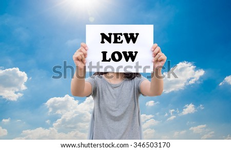 New low stats concept of stock market by asian women show the signboard with blue sky background - stock photo