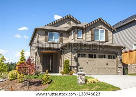new luxury family house with landscaping on the front and blue sky on background
