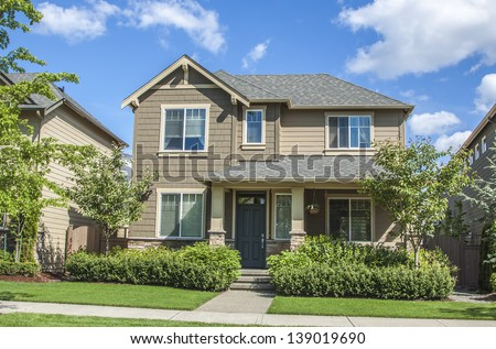 new luxury family house with landscaping on the front and blue sky on background and green grass on front   - stock photo
