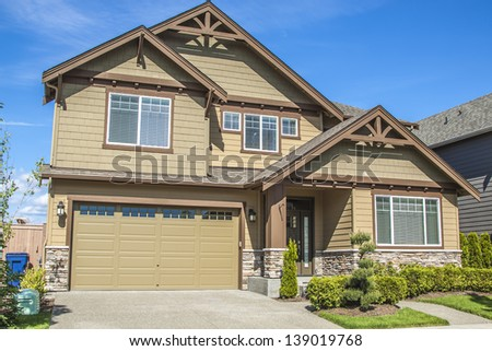new luxury family house with landscaping on the front and blue sky on background and green grass on front