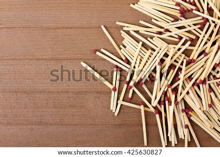 new matches scattered on a brown wooden background