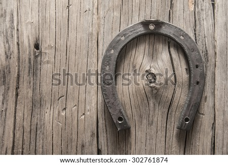 New metal horseshoe on old retro vintage aged wooden background Empty space for inscription or object Symbol of lucky - stock photo