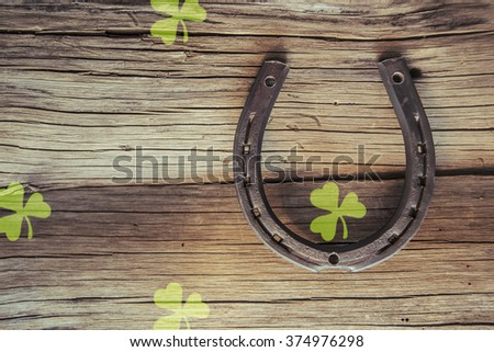 New metal horseshoe with four leaf clover on old retro vintage aged wooden background Empty space for inscription or object Symbol of lucky - stock photo