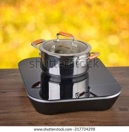 new metal pots in the kitchen on induction hob - stock photo