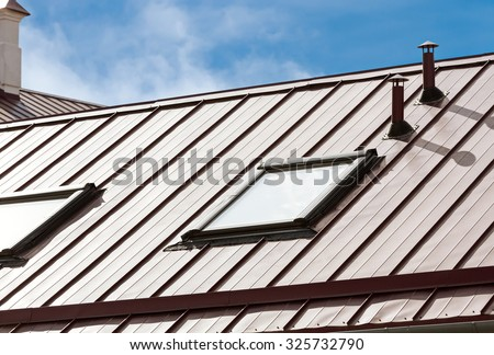 new metal roof with skylights against blue sky - stock photo