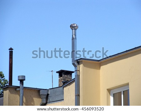 New metal ventilation chimneys on the roof one with rotor on top.                               - stock photo