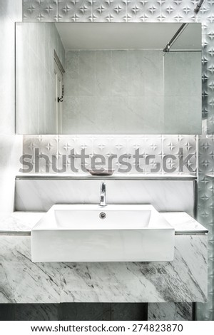 New mirror and ceramic washbasins on granite counter in modern restroom - stock photo