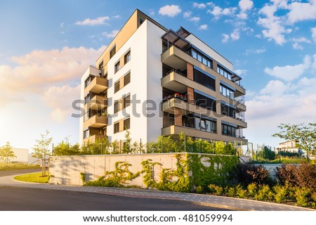 New modern block of flats in green area with blue sky