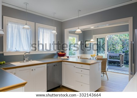 New modern kitchen interior with bar and breakfast area. Brightly lit, light blue walls, counter tops, stainless steel appliances. - stock photo