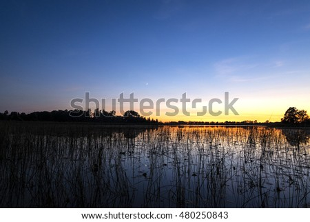 New Moon at Sunset Over a Lake