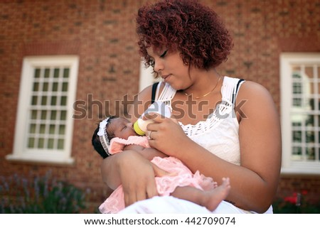 New mother feeding her baby - stock photo
