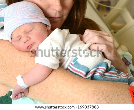 new mother holding a sleeping newborn infant in hospital - stock photo