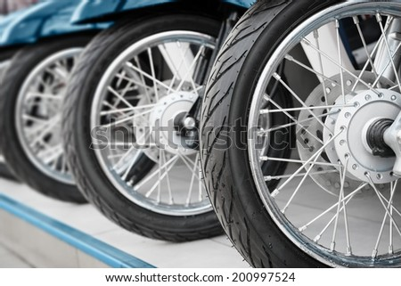 New motorcycles standing in the row closeup on wheels - stock photo