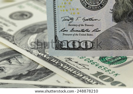 new one hundred dollar note on heap of old notes