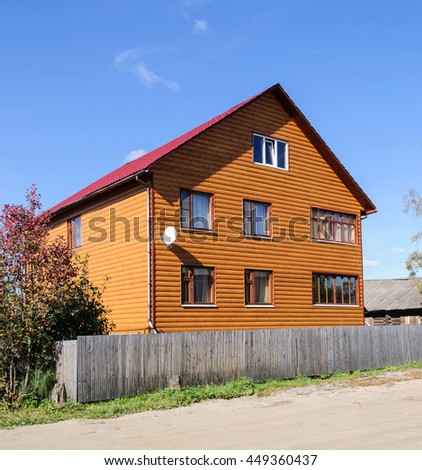 New orange two-storey wooden house behind the old wooden fence, sunny summer day