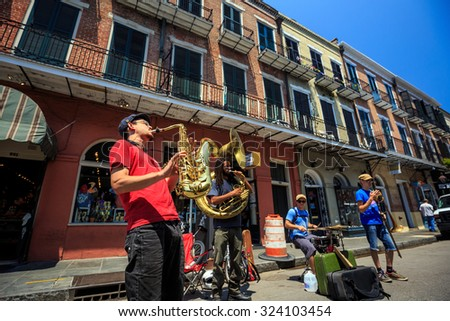 NEW ORLEANS - AUGUST 25: The French Quarter in New Orleans on August 25, 2015, a jazz band plays jazz melodies in the street for donations from the tourists  - stock photo