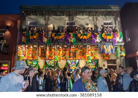New Orleans, LA/USA - circa March 2011: People throwing beads and watching celebration from balconies during Mardi Gras in New Orleans, Louisiana - stock photo