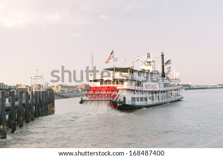 NEW ORLEANS, LOUISIANA - AUGUST 2:  An old time steamboat leaves the dock and heads into the Mississippi River on August 2, 2010 in the French Quarter of New Orleans. - stock photo