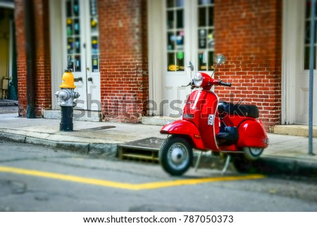 New Orleans, Louisiana /USA - June 25 2017: Ancient district of New Orleans, French Quarter. Old-fashioned red scooter on the streets of the French Quarter in New Orleans.