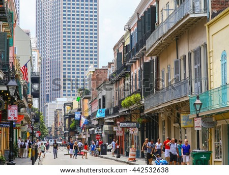 NEW ORLEANS, USA - MAY 14, 2015: View of Royal Street in French Quarter with its historic architecture, in the back modern highrises. Many people are strolling down the street.