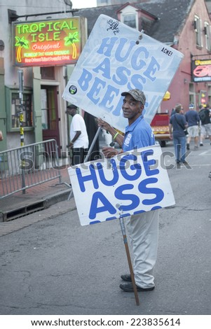 "NEW ORLEANS, USA - OCTOBER 10, 2014: Beer promoter carries ""Huge Ass Beer"" signs on Bourbon Street in New Orleans. - stock photo"