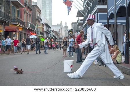 NEW ORLEANS, USA - OCTOBER 10, 2014: Man dressed in white suit and patriotic hat stands frozen in stride on Bourbon Street as if walking a small stuffed dog. - stock photo