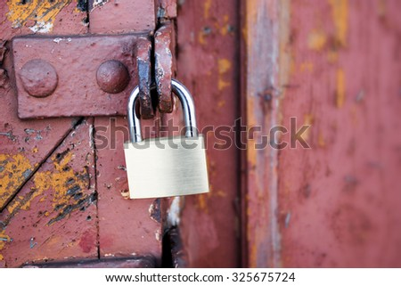new padlock on an old red wooden gate, selected focus, narrow depth of field, copy space in the blurry background - stock photo
