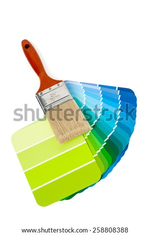 New paint brush and colorful green and blue paint chips for home improvement isolated on white background - stock photo