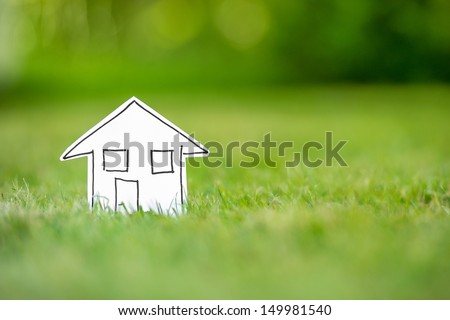 New paper house in grass - stock photo