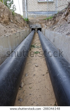 new plastic modern technology black heating pipes in trench near city house - stock photo
