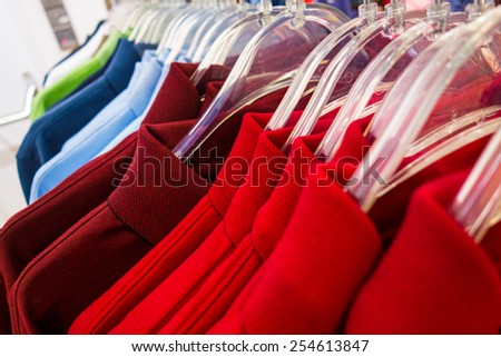 New polo shirts aligned on hangers in fashion store