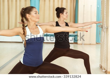 New poses. Portrait of two beautiful healthy women practicing warrior pose in yoga class - stock photo